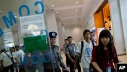 Sekelompok mantan budak nelayan dikawal polisi Myanmar tiba di bandar udara internasional Yangon, Mei 2015. (AP/Gemunu Amarasinghe)