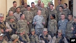 In this image released by the U.S. Department of Defense and taken Monday, Aug. 20, 2012, Army Gen. Martin E. Dempsey, chairman of the Joint Chiefs of Staff, talks to American service members with International Security Assistance Forces in Kabul, Afghani