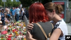 Warga mengenang korban penembakan di pusat perbelanjaan Olympia, Munich hari Minggu sore (24/7).