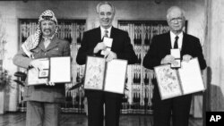 PLO leader Yasser Arafat, left, Israeli Prime Minister Yitzhak Rabin, center, and Israeli Foreign Minister Shimon Peres pose with their medals and diplomas, after receiving the 1994 Nobel Peace Prize in Oslo's City Hall, Dec. 10, 1994.