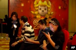 FILE - In this photo taken Feb. 2, 2015, a woman browses her smartphone near other attendees at a press conference in Beijing.