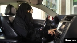 FILE - A woman drives a car in Saudi Arabia, Oct. 22, 2013.