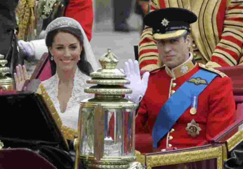 Britain's Prince William and his wife Kate, Duchess of Cambridge, left, wave as they leave Westminster Abbey at the Royal Wedding in London Friday, April 29, 2011. (AP Photo/Alastair Grant)