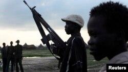 Kijana wa kabila la Luo Nuer akiwa amebeba bunduko huku akitembea kwenda nyumani kwenye jimbo la Yuai Uror, Sudan Kusini Julai 23, 2013.