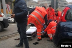 Medical personnel take care of an injured person who was hit by gunfire from a vehicle in Macerata, Italy, Feb. 3, 2018.