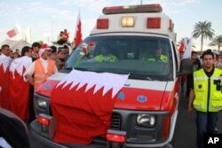 An ambulance draped in a Bahraini flag