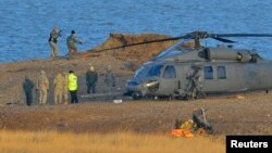 A Pave Hawk helicopter, military personnel and emergency services attend the scene of a helicopter crash on the coast near the village of Cley next the Sea in Norfolk, eastern England, Jan. 8, 2014.