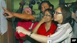 Relatives inspect the list of passengers on board a missing Russian airplane at Halim Perdanakusuma Airport in Jakarta, Indonesia, May 9, 2012.