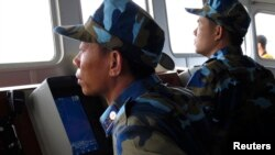FILE - Crewmen aboard a Vietnam coastguard ship look at a Chinese navy frigate on a screen, in disputed waters close to the Haiyang Shiyou 981, known in Vietnam as HD-981, oil rig in the South China Sea, July 15, 2014.