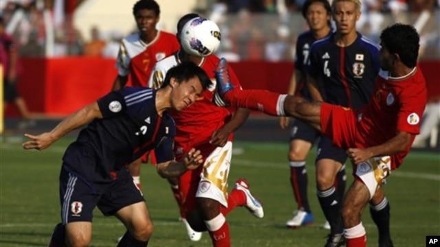 Shiji Okazaki, kiri, menyundul bola dan berhasil menyarangkan gol selagi Rashid Alfarsi berusaha menggagalkannya. Gol pada menit-menit terakhir itu membuat Jepang menang 2-1 atas Oman (foto, 11/14/2012).