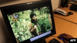 FILE - A Pakistani journalist watches a newly released video of radical cleric Maulana Fazlullah in Peshawar, July 23, 2010.