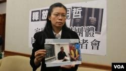 李明哲的妻子李淨瑜向媒體展示李明哲以往活動的照片(美國之音楊明拍攝 資料照片)