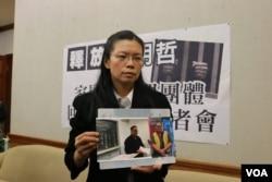 李明哲的妻子李净瑜向媒体展示李明哲以往活动的照片(美国之音杨明拍摄)