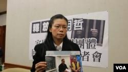 李明哲的妻子李淨瑜向媒體展示李明哲以往活動的照片(美國之音楊明拍攝)