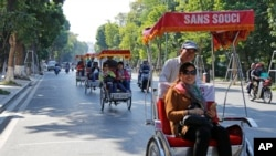 FILE - Chinese tourists ride rickshaws for sightseeing in Hanoi, Vietnam.