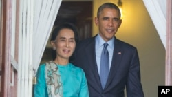 FILE - President Barack Obama walks out with Myanmar's Aung San Suu Kyi at her home before the start of their joint news conference in Yangon, Myanmar.