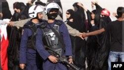 Người biểu tình chống chính phủ cầm cờ Bahrain đứng gần cảnh sát chống bạo động trong làng Abu Saiba, Bahrain, Thứ Bảy, 17/12/2011