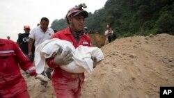 Một nhân viên cứu hỏa mang xác một em bé được tìm thấy từ nơi xảy ra đất chuồi ở Guatemala hôm 2/10.