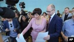 烏克蘭臨時總理亞采紐克(右)與夫人前往投票