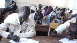 South Sudan has introduced new textbooks for school children, shown here sitting an exam in a school on March 20, 2013,. (VOA/Hou Akot Hou)