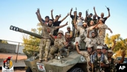 U.S.-backed forces celebrate re-taking Sirte, Libya from the Islamic State group Thursday, Aug. 11, 2016.