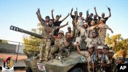 Pasukan Libya yang didukung AS merayakan kemenangan atas ISIS di Sirte, Libya (11/8) lalu.