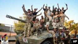 Pasukan yang didukung AS merayakan pengambilalihan kota Sirte di Libya dari ISIS (11/8).