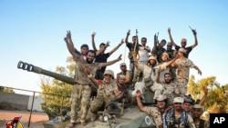 Les forces soutenues par les USA célèbrent la reprise de Syrte, en Libye, au groupe Etat islamique, le jeudi 11 août 2016. Cette ville est le dernier bastion du groupe Etat islamique dans ce pays d'Afrique du Nord. (Albinyan Al Marsous Operation Media Center via AP)