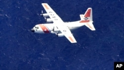 FILE - A U.S. Coast Guard C-130 aircraft flies in a search pattern in waters off the southwest coast of Eleuthera in the Bahamas, Aug. 2, 2003.