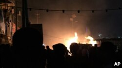 Small restaurants burn after a car bomb attack in the Shiite district of Baghdad's Sadr City, Dec. 4, 2014.