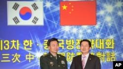 韩国国防部次官白承周(右)与中国人民解放军副总参谋长王冠中在首尔参加第三次韩中国防战略对话。(2013年11月28日)