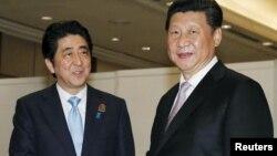 PM Jepang Shinzo Abe (kiri) berjabat tangan dengan Presiden China, Xi Jinping sebelum pertemuan bilateral di Jakarta, Rabu (22/4).