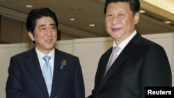 Japan's Prime Minister Shinzo Abe (L) shakes hands with China's President Xi Jinping at the start of their bilateral meeting on the side lines of the Asian-African Conference in Jakarta, in this photo released by Kyodo, April 22, 2015.