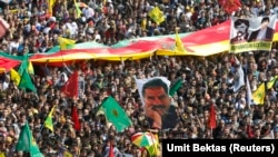 People wave Kurdish flags and hold up a picture of jailed Kurdish militant leader Abdullah Ocalan (C) of the Kurdistan Workers Party (PKK) during a gathering celebrating Newroz, which marks the arrival of spring and the new year, in Diyarbakir March 21, 2