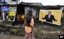 Une femme passant devant une affiche d'Alpha Condé à Conakry