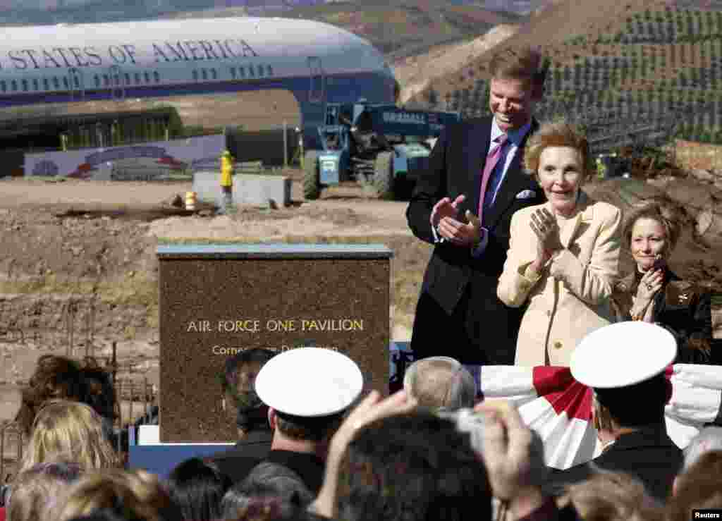 Former U.S. first lady Nancy Reagan applauds after unveiling the cornerstone for a new pavilion to house the former Air Force One (background L), during a dedication ceremony at the Ronald Reagan Presidential Library in Simi Valley, California, Feb. 6, 2004.