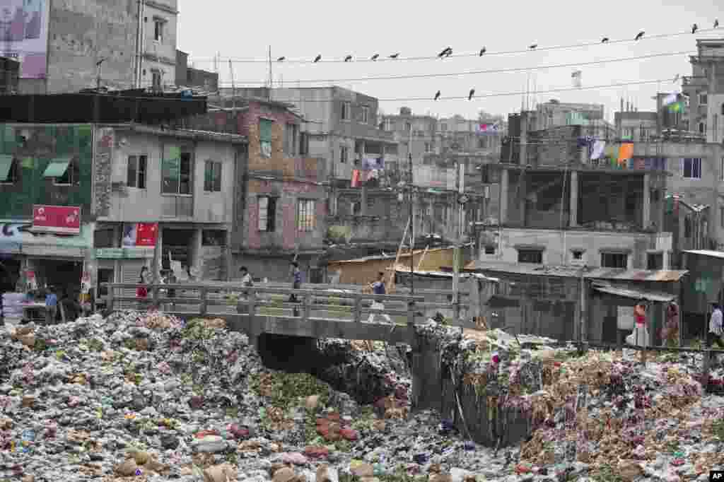 People walk across a bridge on the river Buriganga, choked with plastic and other waste, in Dhaka, Bangladesh.