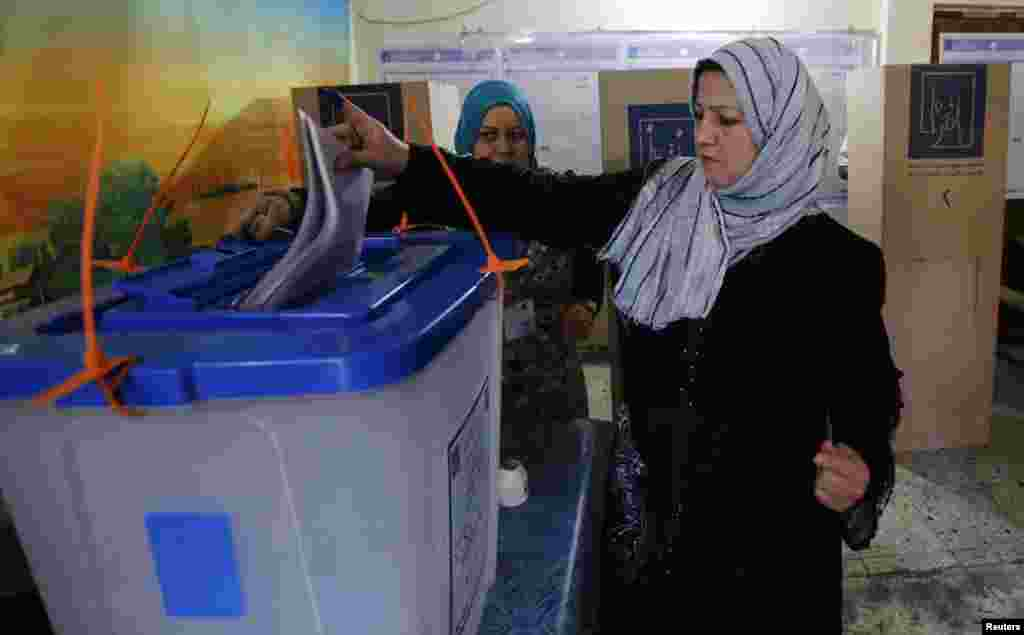 A resident casts her vote at a polling station during parliamentary election in Baghdad, April 30, 2014.