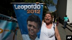 "FILE - A supporter of Leopoldo Lopez shouts ""Freedom for Leopoldo"" while holding his poster outside court in Caracas, Venezuela."
