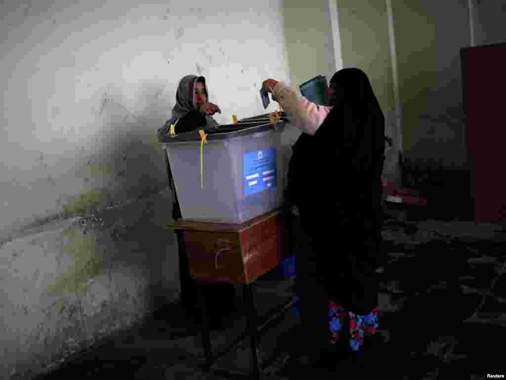 قدامت پسند تصور کیے جانے والے افغانستان میں ایک خاتون ووٹ ڈال رہی ہیں۔