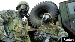 U.S. soldiers wear gas masks as they take part in a chemical, biological and radiological warfare exercise.