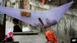 "FILE - A woman laborer pacifies her child while cleaning a manhole on a sidewalk in Mumbai, India. Approved in September 2015, the sweeping 15-year agenda approved by the 193 U.N. member states is a global ""to-do"" list to tackle such issues as climate change, education, hunger, joblessness and land degradation."