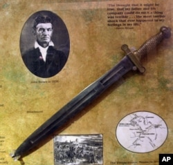 FILE - A photo of abolitionist John Brown is seen at the John Brown Museum in Osawatomie, Kansas, May 17, 2000, with a broadsword similar to ones used by Brown and his sons.