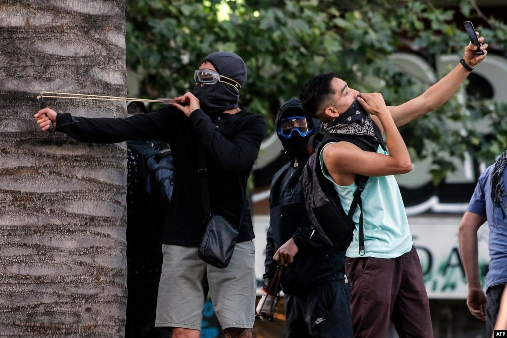 A demonstrator takes a selfie as another one uses a sling during a protest against the government's economic policies in Santiago, Chile, Nov. 6, 2019.