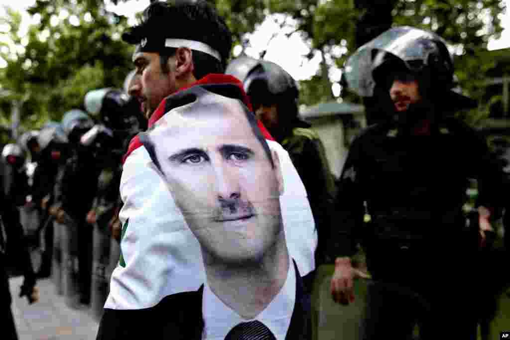 Một người Syria khoác lá cờ Syria có ảnh của Tổng thống Assad đi ngang qua cảnh sát trong cuộc biểu tình chống Israel trước văn phòng của Liên Hiệp Quốc tại Tehran. Iran lên án cuộc không kích Syria của Israel và kêu gọi các nước trong vùng phản đối cuộc tấn công này.