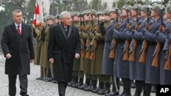 FILE - US Secretary of Defense Chuck Hagel (center) and Polish Defense Minister Tomasz Siemoniak inspect a military honor guard during a welcoming ceremony in Warsaw, Jan. 30, 2014.