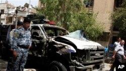 Pripadnici bezbednosti vrše uviđaj na jednom od poprišta današnjih bombaških napada u Bagdadu