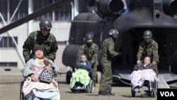 Soldados japoneses realizan tareas de evacuación, movilizando a los ancianos a lugares seguros y con mejor atención.