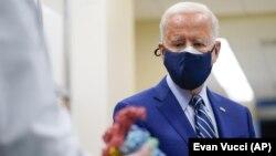 President Joe Biden looks at a model of Covid-19 as he visits the Viral Pathogenesis Laboratory.