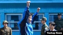 한국 전남 여수 인근 공해상에서 한국 해경에 구조된 북한 선원이 6일 판문점을 통해 북한으로 넘어가기에 앞서 만세를 부르고 있다. 구조된 선원은 3명이고 시신 2구도 송환됐다
